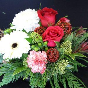 White flowers beside lush red roses